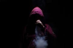 Vapingsmens die mod. houden Een wolk van damp Zwarte achtergrond Vaping een elektronische sigaret met heel wat rook royalty-vrije stock afbeelding