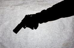 Vapnet i handen av män som är klar att skjuta på hans offer Avbrott av lagen och av brottet Attack med ett vapen Suluet på a royaltyfri foto