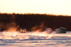 Vapor coming out of the lake where it`s not completely frozen, while ice fishing huts are already installed stock photo