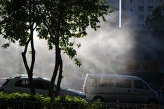 Vapor de agua en luz del sol en una calle con los coches en Urumqi, Xinjiang, China imagen de archivo