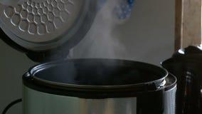 Vapor en un multicooker de cocinar con una tapa abierta en una cocina metrajes