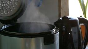Vapor en un multicooker de cocinar con una tapa abierta en una cocina almacen de metraje de vídeo
