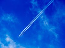 Vapor trails. Airplane flying through blue sky with slight cloud with four vapor trails Royalty Free Stock Images