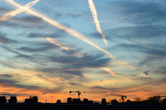 Vapor trails and clouds in a blue and orange sky. Vapor trails and thin clouds in a blue and orange sky with a rooftop skyline at the bottom Royalty Free Stock Photo