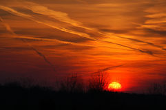 Vapor Trails at Sunset. A sunset full of brilliant colors is criss-crossed with a number of vapor trails Stock Photography