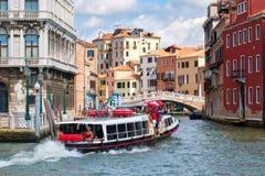 Vaporetto o el autobús del agua en un canal en Venecia rodeó por los edificios coloful viejos Foto de archivo