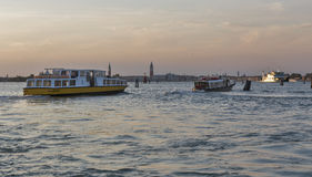Vaporetto sails in Venice lagoon at sunset, Italy. Stock Photos