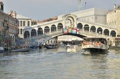 Vaporetto som korsar den Rialto bron Arkivfoto