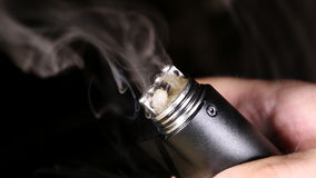 Vaporizer mechanical mod firing with cotton and e-juice. On dual coil build. Macro shot stock video