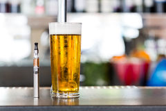 Vaporizer pipe and glass of beer Royalty Free Stock Photos