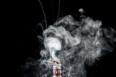 Vaporizer tank with cloud of smoke. RDA Mage coilart tank on black studio background Stock Photo