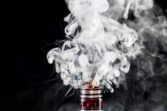 Vaporizer tank with cloud of vapor. RDA Mage coilart tank vaporising glycerine liquid stock image