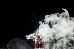Vaporizer tank with cloud of vapor. RDA Mage coilart tank vaporising glycerine liquid royalty free stock photography