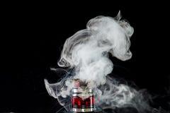 Vaporizer tank with cloud of vapor. RDA Mage coilart tank vaporising glycerine liquid stock photography