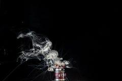 Vaporizer tank with cloud of vapor. RDA Mage coilart tank vaporising nicotine liquid royalty free stock photo