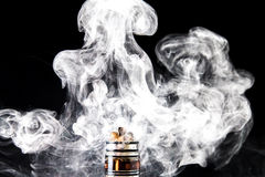 Vaporizers steam cloud. Vaporizer smoke explosion on isolated black background in studio with e-cigarette coil and tank Royalty Free Stock Photo