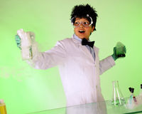 Vaporizing Solution. A young mad scientist exclaiming over his vaporizing solution in one hand, while holding a green, bubbly solution in the other Royalty Free Stock Images