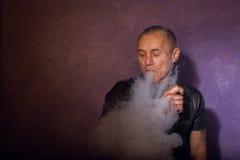 Vaporizzatore di fumo tatuato serio dell'uomo, nuvole dei rilasci del vapore Immagini Stock Libere da Diritti