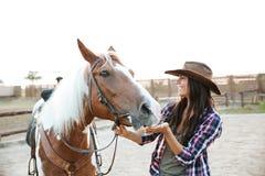 Vaqueira alegre da mulher que joga com o cavalo no campo Foto de Stock Royalty Free