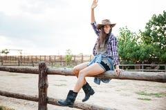 Vaqueira alegre da mulher que senta-se na cerca e que tem o divertimento Fotos de Stock