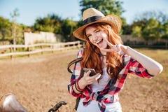 Vaqueira alegre da mulher que usa o telefone celular e mostrando o sinal de paz Foto de Stock Royalty Free