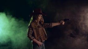 A vaqueira guarda um revólver em suas mãos e em visar o bandido Fundo preto do fumo Movimento lento Vista lateral filme
