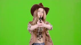 A vaqueira guarda um revólver em suas mãos e em visar o bandido Tela verde vídeos de arquivo