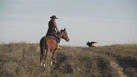 Vaqueira nova no cavalo marrom com o cão de corrida no movimento lento fora video estoque
