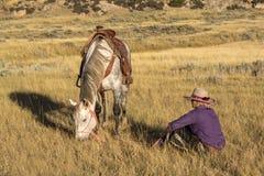Vaqueira que senta-se pelo cavalo imagem de stock