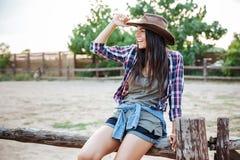 Vaqueira relaxado alegre da jovem mulher que senta-se na cerca e no sorriso Imagens de Stock