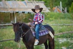 Vaqueiro considerável do menino do fermer bonito nas calças de brim que aprecia o dia de verão na vida da vila com as flores que  fotos de stock royalty free