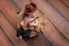 Vaqueiro recém-nascido Playing do bebê uma guitarra minúscula fotografia de stock royalty free