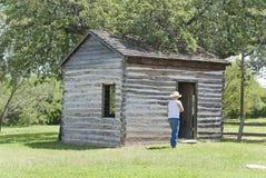 Vaqueiro Walking Toward uma cabana rústica de madeira imagens de stock royalty free
