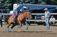 Vaquera adolescente joven en el caballo que compite con justo del país Fotos de archivo