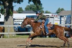 Vaquera adolescente joven en el caballo que compite con justo del país Imagen de archivo libre de regalías