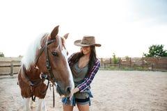Vaquera alegre de la mujer que coloca y que toma cuidado de su caballo Fotos de archivo