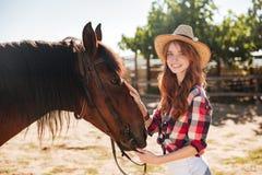 Vaquera bastante preciosa que toma cuidado de su caballo en rancho Fotos de archivo