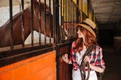 Vaquera bonita de la mujer que coloca y que mira el caballo en establo Foto de archivo libre de regalías