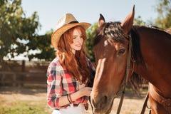 Vaquera de la mujer que toma cuidado de su caballo en rancho Imágenes de archivo libres de regalías