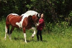 Vaquera feliz de la mujer con su caballo Foto de archivo libre de regalías
