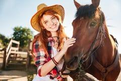 Vaquera feliz de la mujer joven del pelirrojo en sombrero con su caballo Imagen de archivo libre de regalías