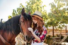 Vaquera feliz de la mujer joven que se coloca con su caballo en rancho Imagenes de archivo