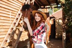 Vaquera feliz de la mujer que coloca y que abraza su caballo imagenes de archivo