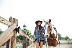 Vaquera hermosa feliz de la mujer joven con su caballo en rancho Imagen de archivo