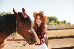 Vaquera hermosa sonriente de la mujer joven con su caballo en granja Fotos de archivo libres de regalías