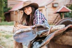 Vaquera morena sonriente de la mujer joven que se inclina en la cerca en pueblo fotos de archivo