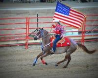 Vaquera patriótica a caballo con la bandera fotografía de archivo