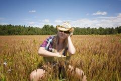 Vaquera que se sienta en campo de trigo Fotos de archivo