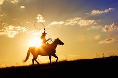 Vaquera roping en horizonte Imagenes de archivo