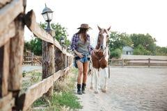 Vaquera sonriente que se sostiene y que camina con su caballo en rancho Imagen de archivo libre de regalías